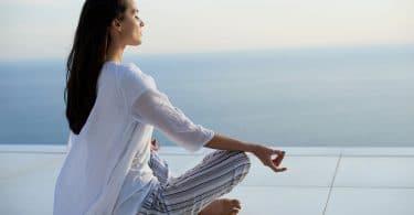 Mulher jovem, vestida de branco, sentada com as pernas cruzadas, meditando, com o mar ao fundo da foto.