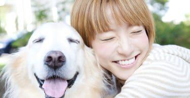 Garota asiática sorrindo e abraçando um cachorro.