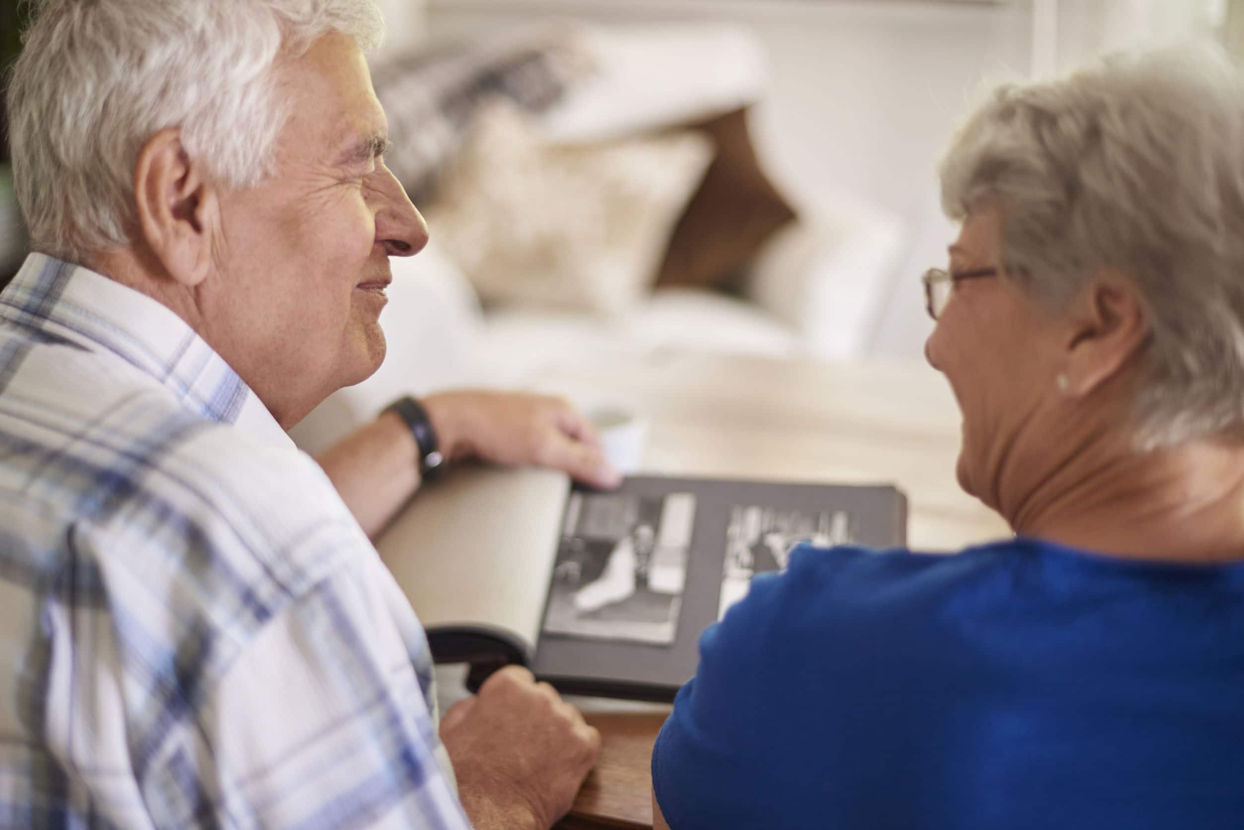 Casal de idosos olhando álbum de fotos.