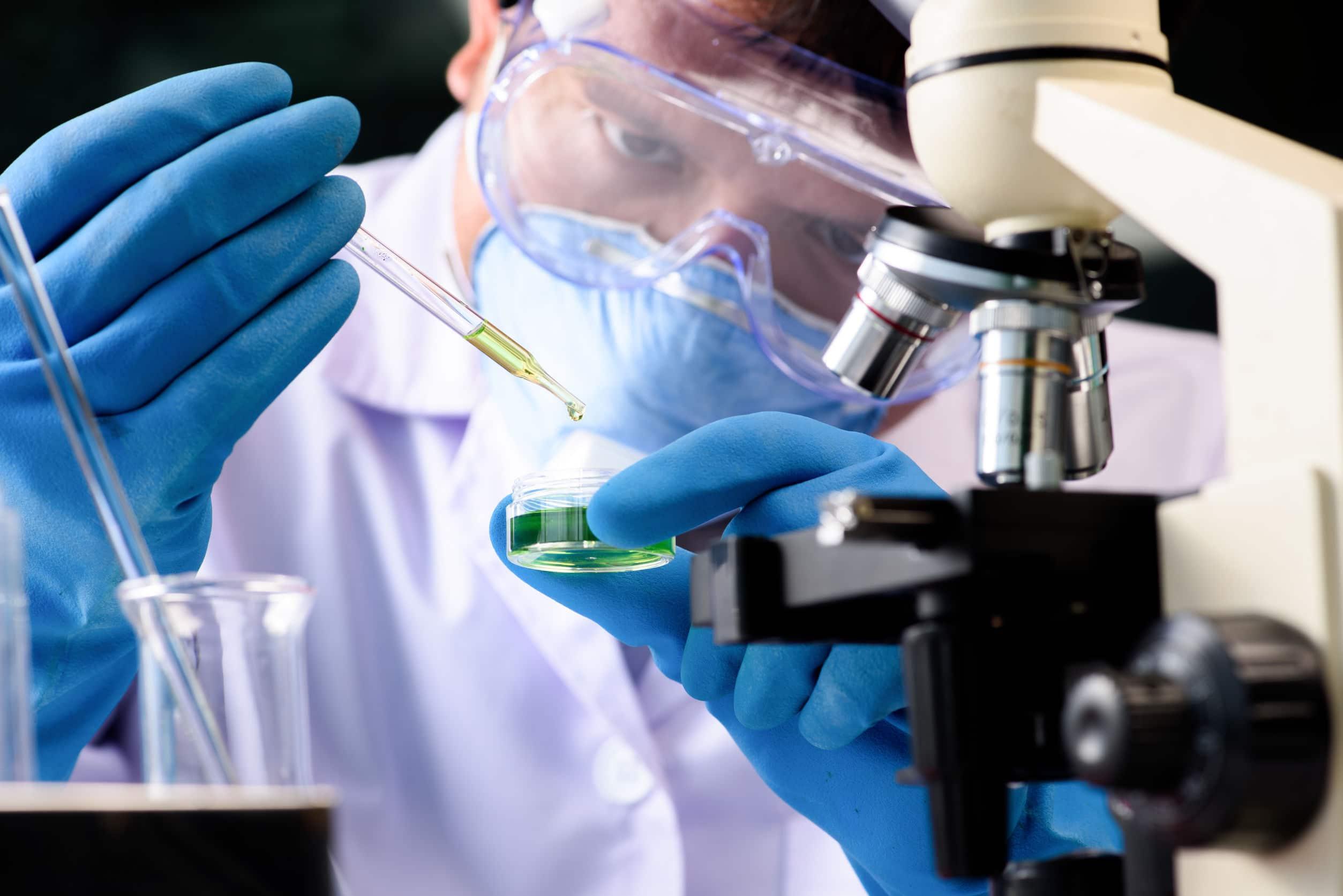 Cientista vestido com equipamentos de proteção despejando um líquido verde com conta gostas em um pote de vidro redondo, perto de um microscópio.