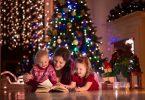 Mãe com dois filhos pequenos sentados no meio da sala com decorações de natal, lendo um livro com as crianças.
