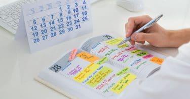 Close em mão de uma pessoa anotando coisas em uma agenda.