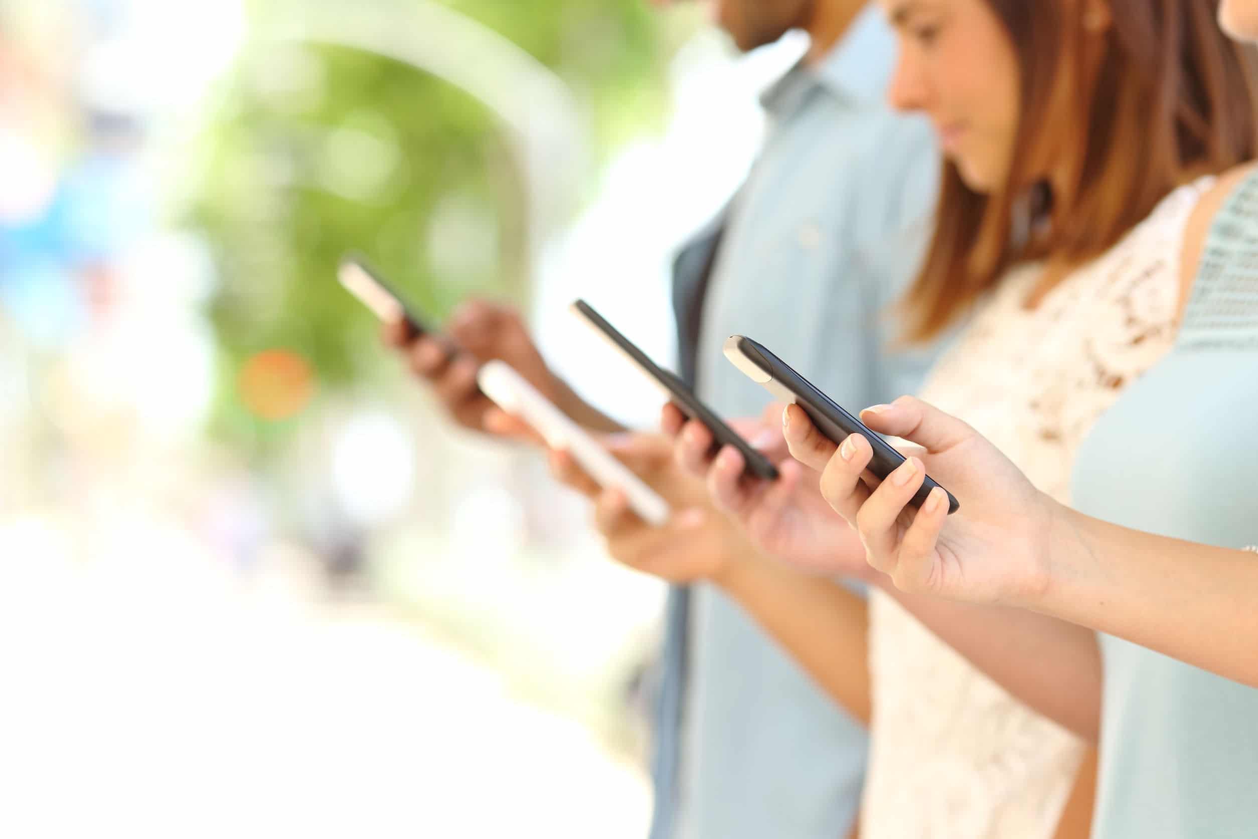 Quatro amigos mandando mensagens pelo celular na rua. Fundo embaçado.