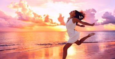 Mulher jovem e sorridente, correndo na praia, a beira mar, com o por do sol ao fundo.
