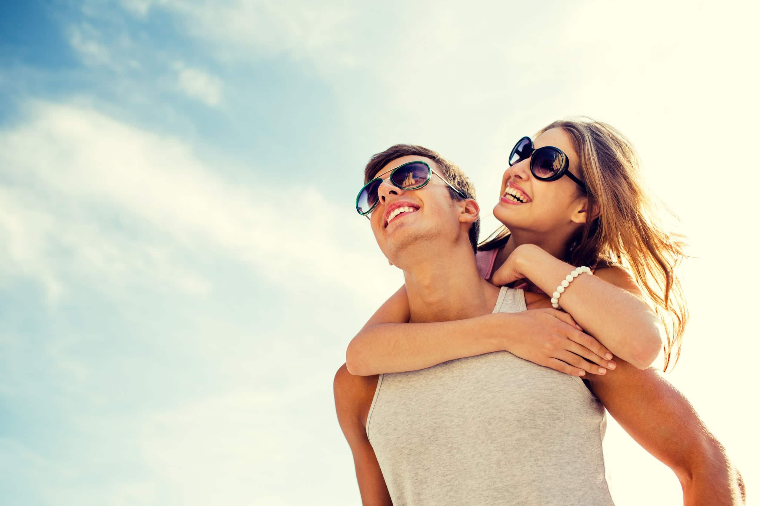 Mulher montada nas costas de homem, ambos usando óculos de sol, com o céu ensolarado ao fundo.