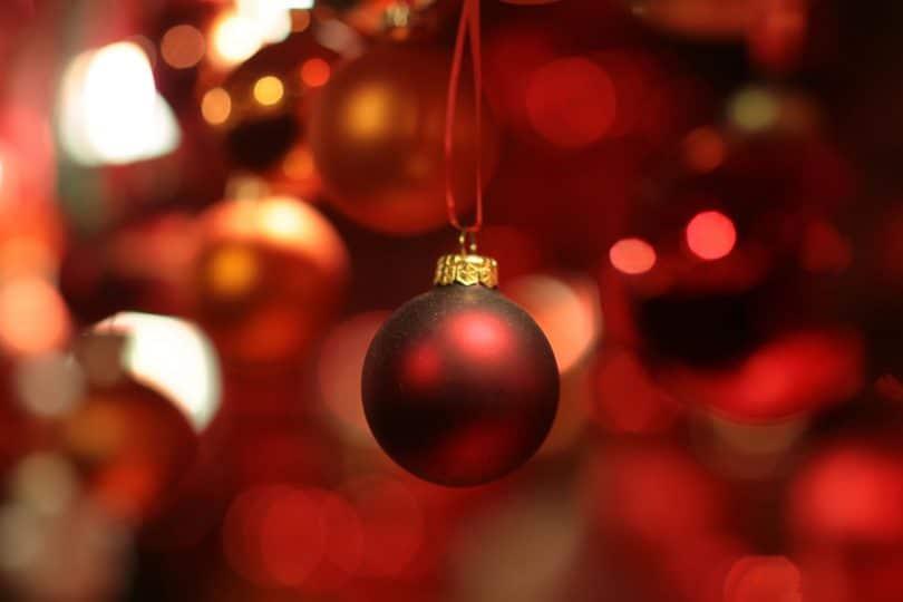 Imagem da decoração natalina pendurada. Bola vermelha em foco.