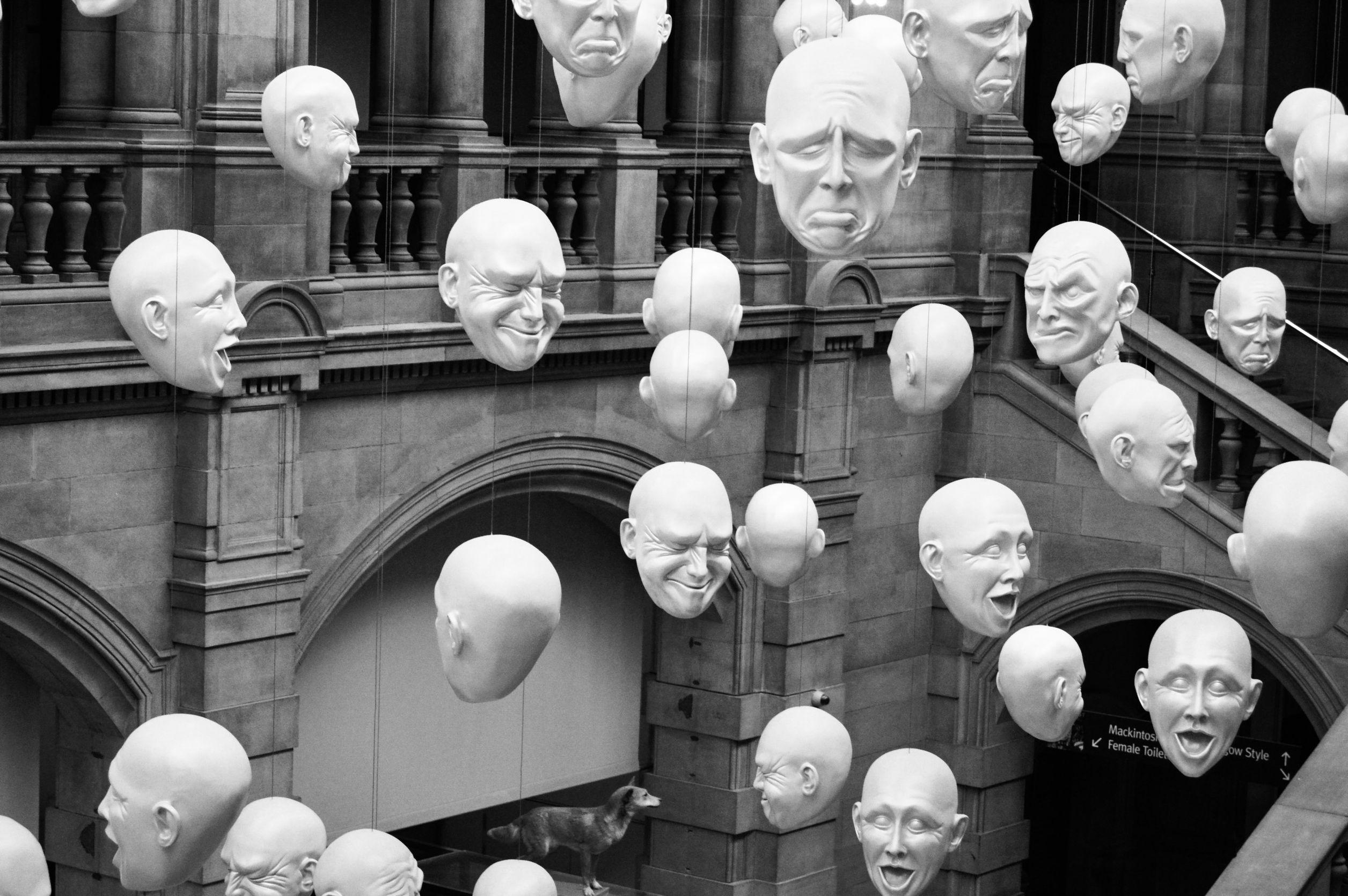 máscaras com várias emoções, todas penduradas em um pátio.