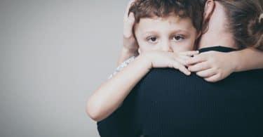 filho triste abraçando sua mãe em casa.