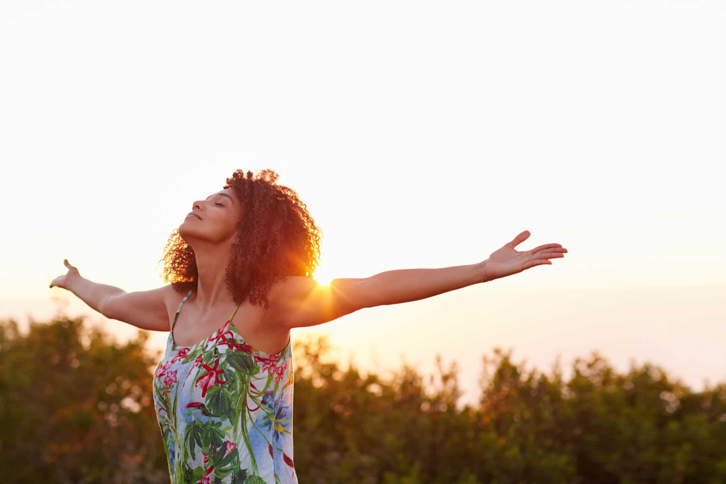 Mulher com cabelo afro com os braços abertos em sinal de gratidão. Fundo de céu ensolarado e grama.