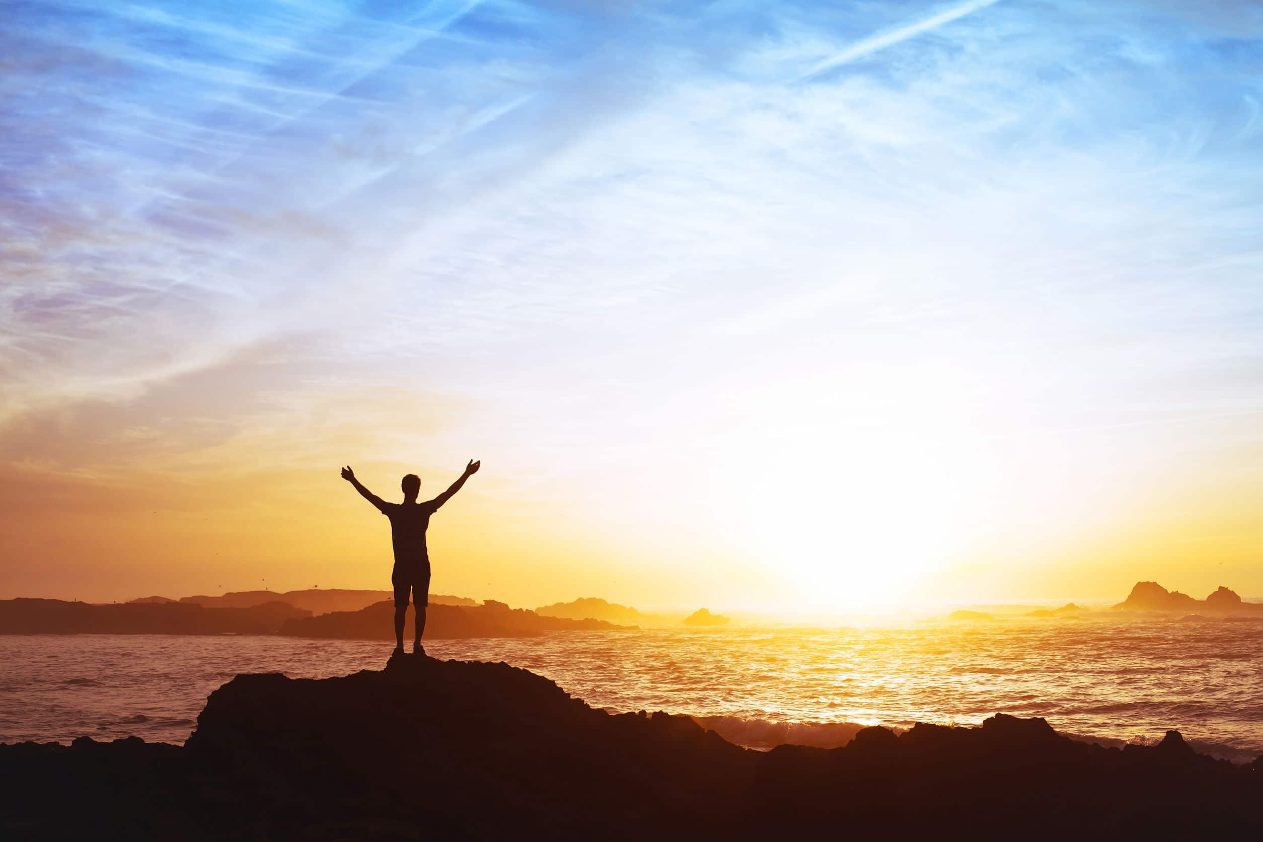 Silhueta de homem em pé em pedras, na frente do mar, observando o pôr do sol.