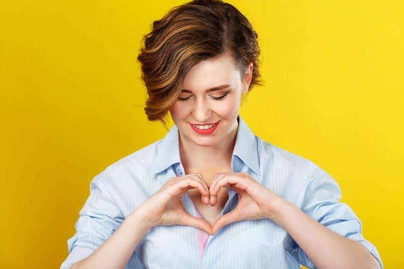 Amor próprio. Mulher fazendo um coração com as mãos. Fundo amarelo