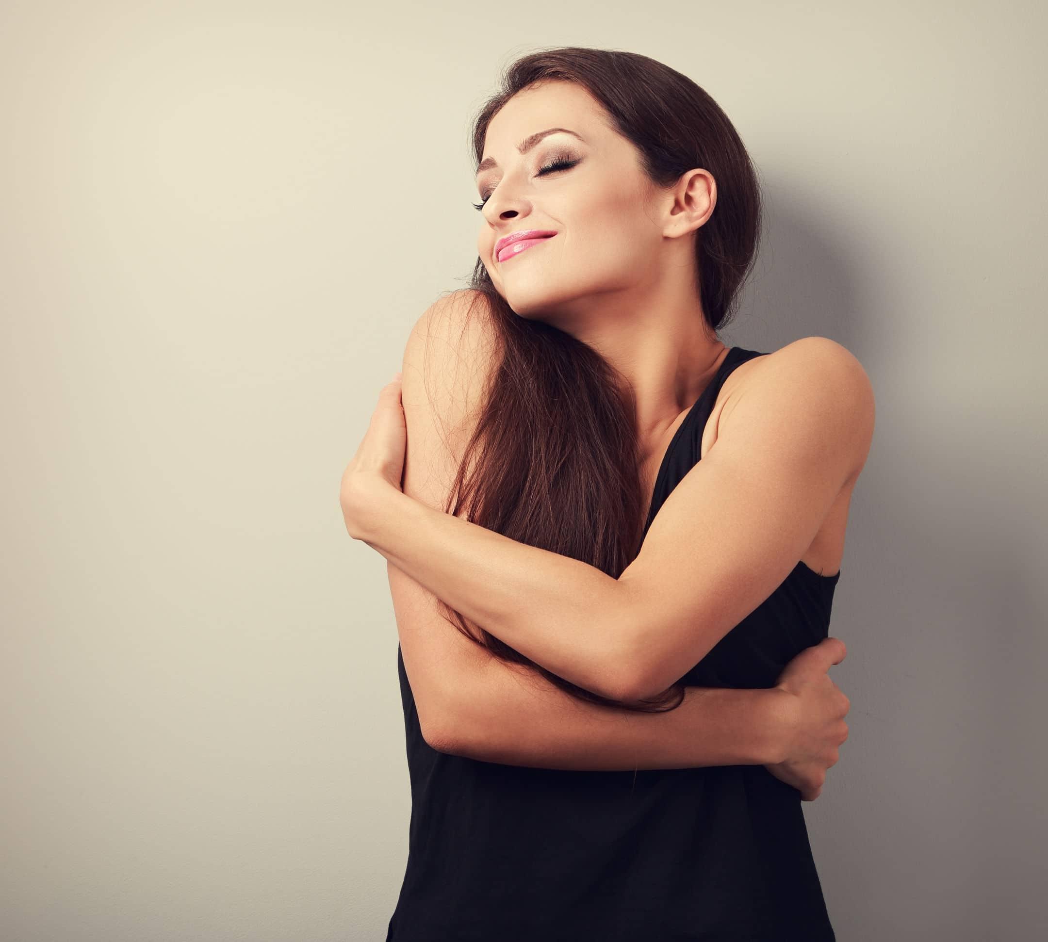 Mulher branca, vestindo regata preta, encostada em uma parede bege, se abraçando.