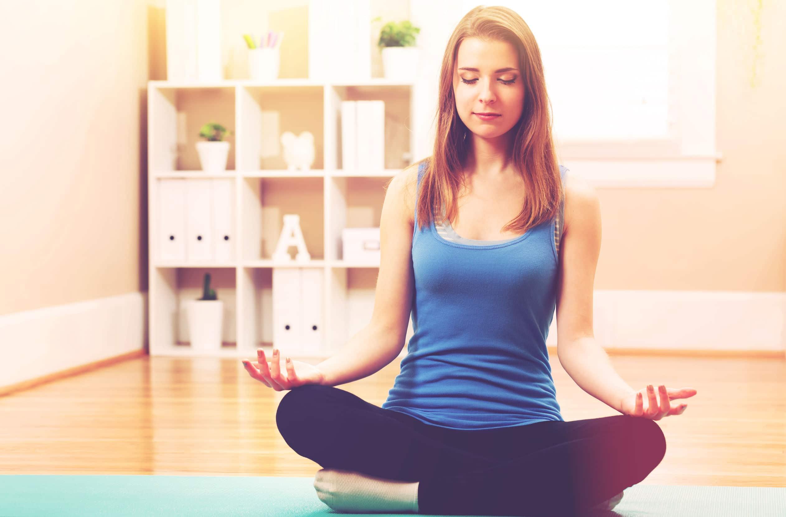 mulher jovem sentada em posição de meditação, com as pernas cruzadas, na sala de sua casa.