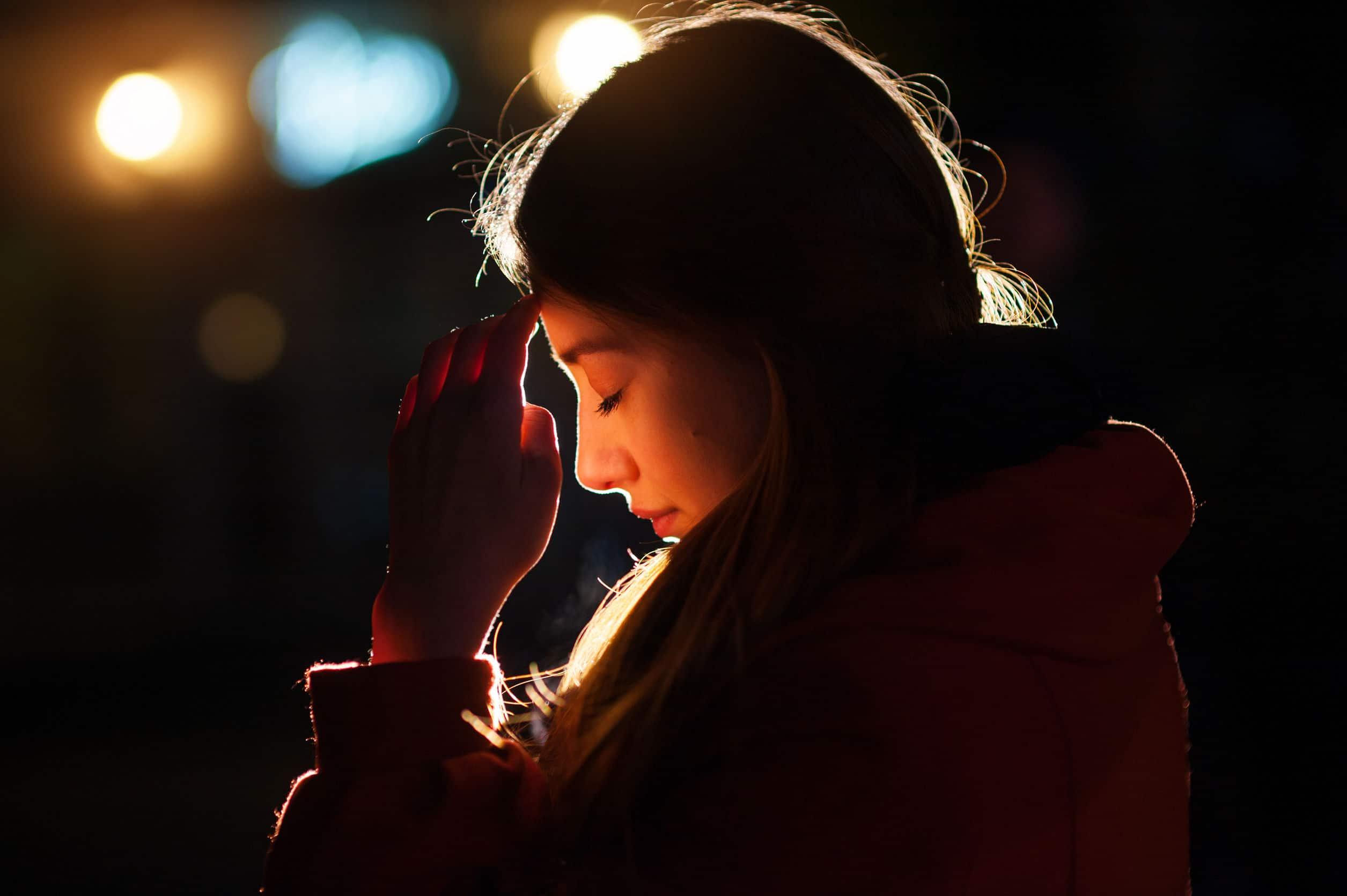 Mulher vestida com roupas de frio, apoiando rosto na mão, em um ambiente escuro com uma luz direcionada ao rosto dela.