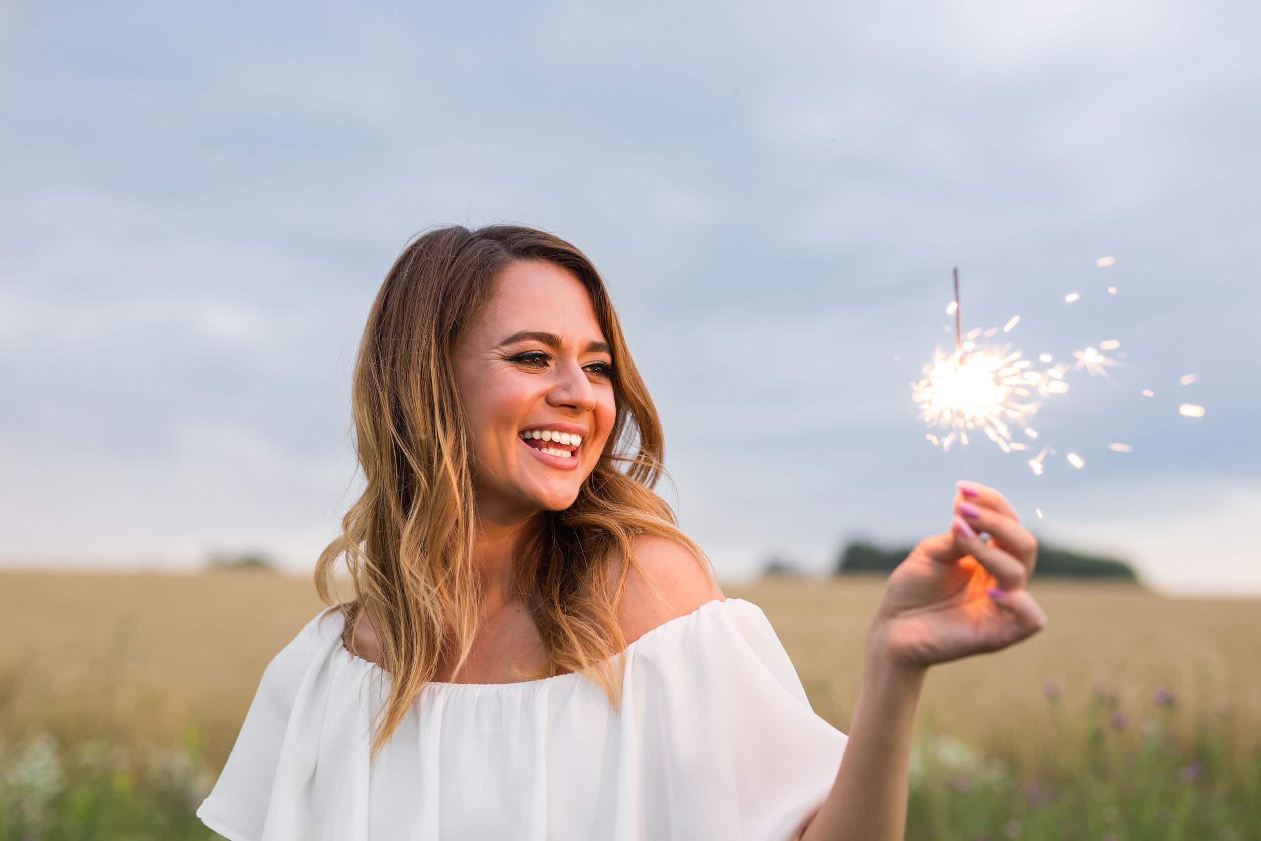 Mulher loira, sorridente em meio de um campo, segurando uma vela que solta faíscas.