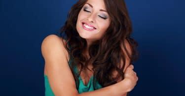 Mulher feliz se abraçando. Fundo azul.