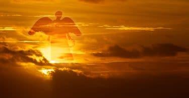 Silhueta de um anjo da guarda no céu. Cena do pôr do sol.