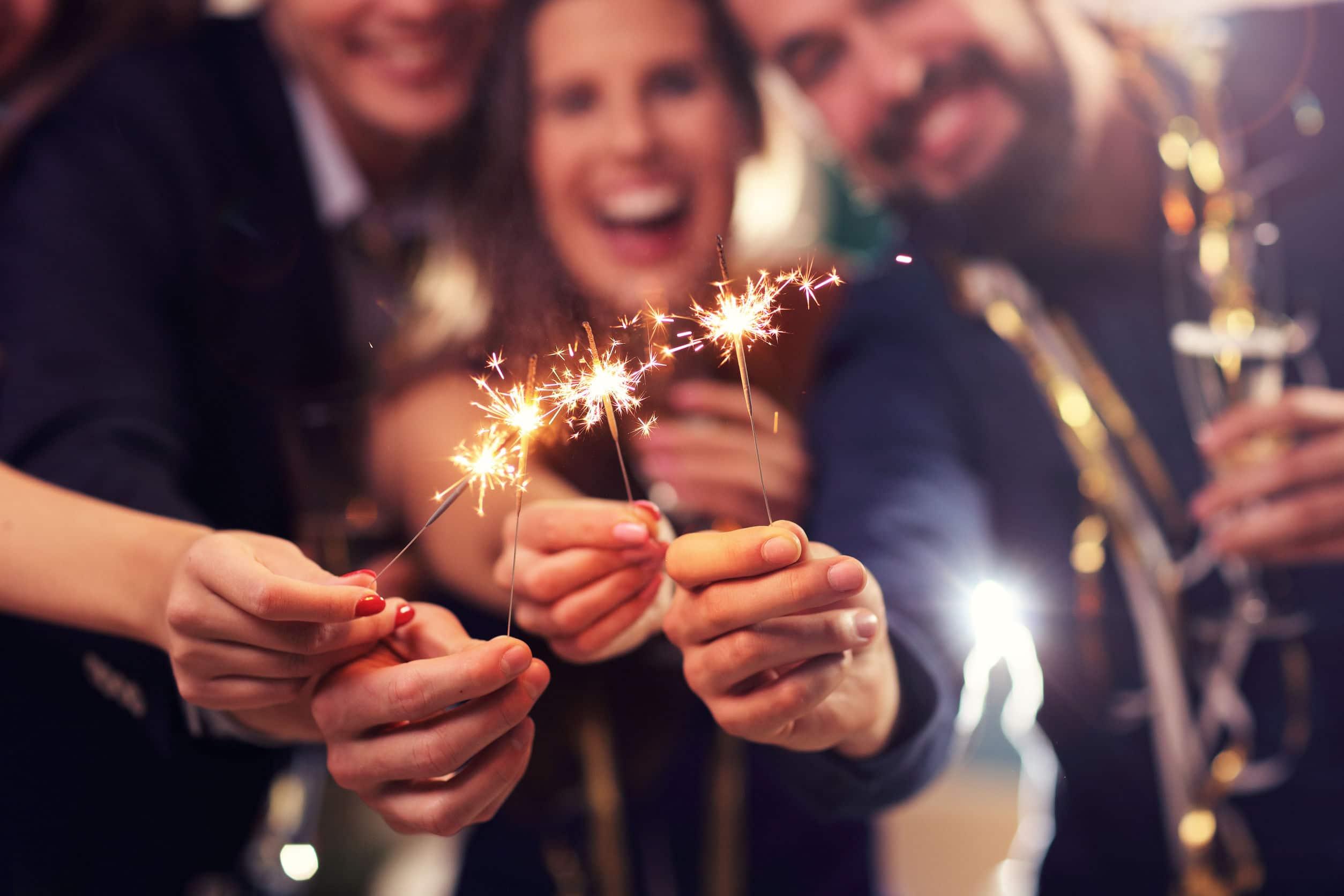 Grupo de amigos, dois homens e uma mulher, sorridentes em uma festa, segurando velas que soltam faíscas acesas e segurando taças de champanhe.