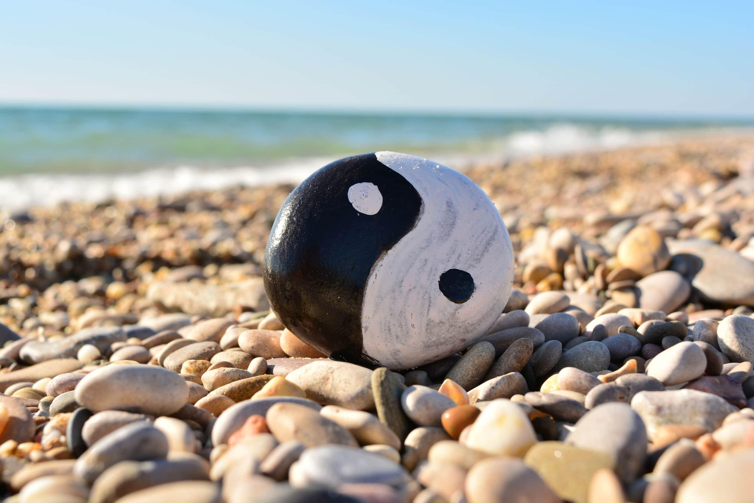 Símbolo do ying yang pintado em uma pedra, na beira mar da praia com céu ensolarado.