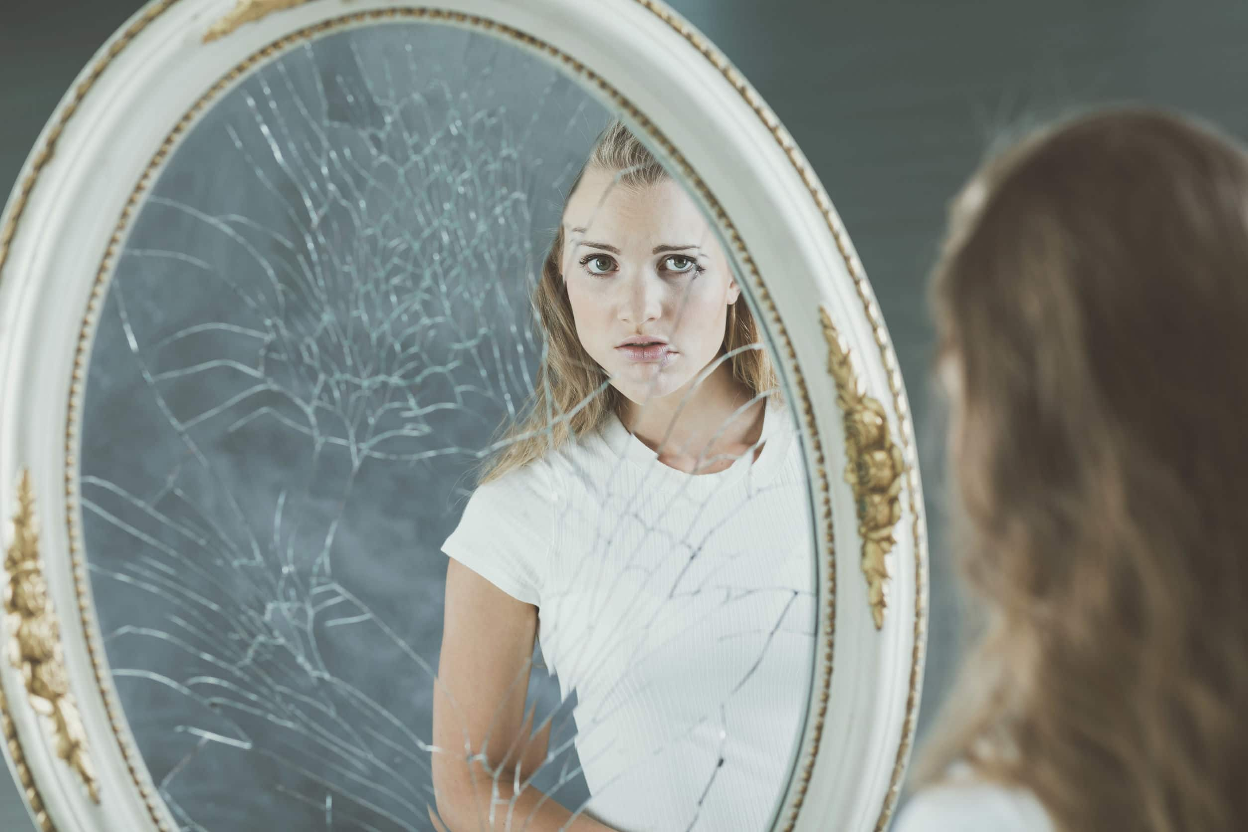 Linda mulher se olhando num espelho quebrado. Conceito de falta de autoestima.
