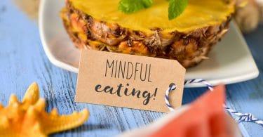 um rótulo de papel marrom com o texto mindful eating na frente de algumas fatias de abacaxi e um pedaço de melancia sobre uma mesa de madeira rústica azul
