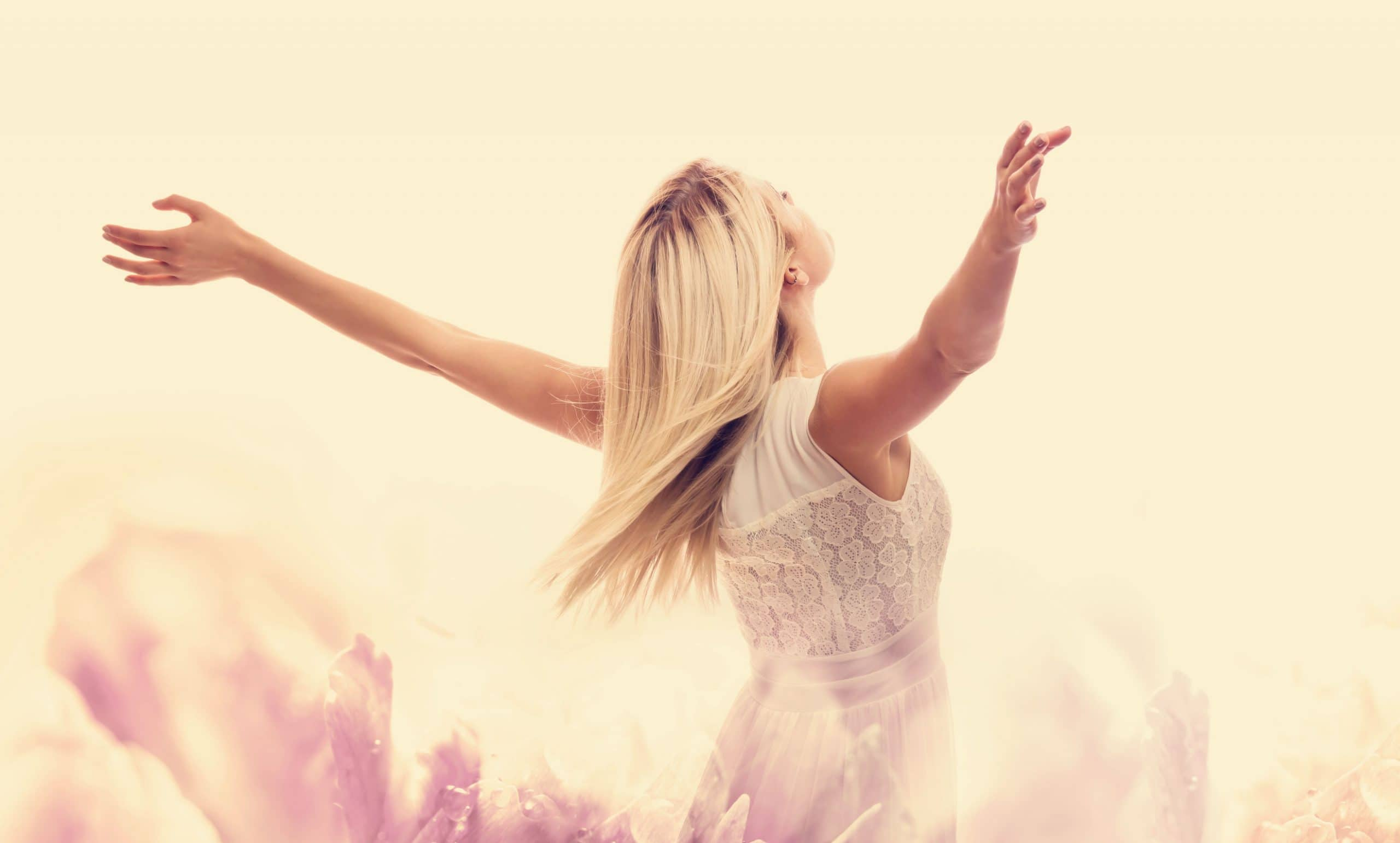 mulher bonita, desfrutando de sua liberdade com os braços abertos no meio de um campo de vegetação.
