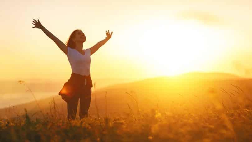 Mulher em pé de braços abertos com sol ao fundo