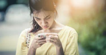 Menina asiática mexendo no celular com cara de séria.