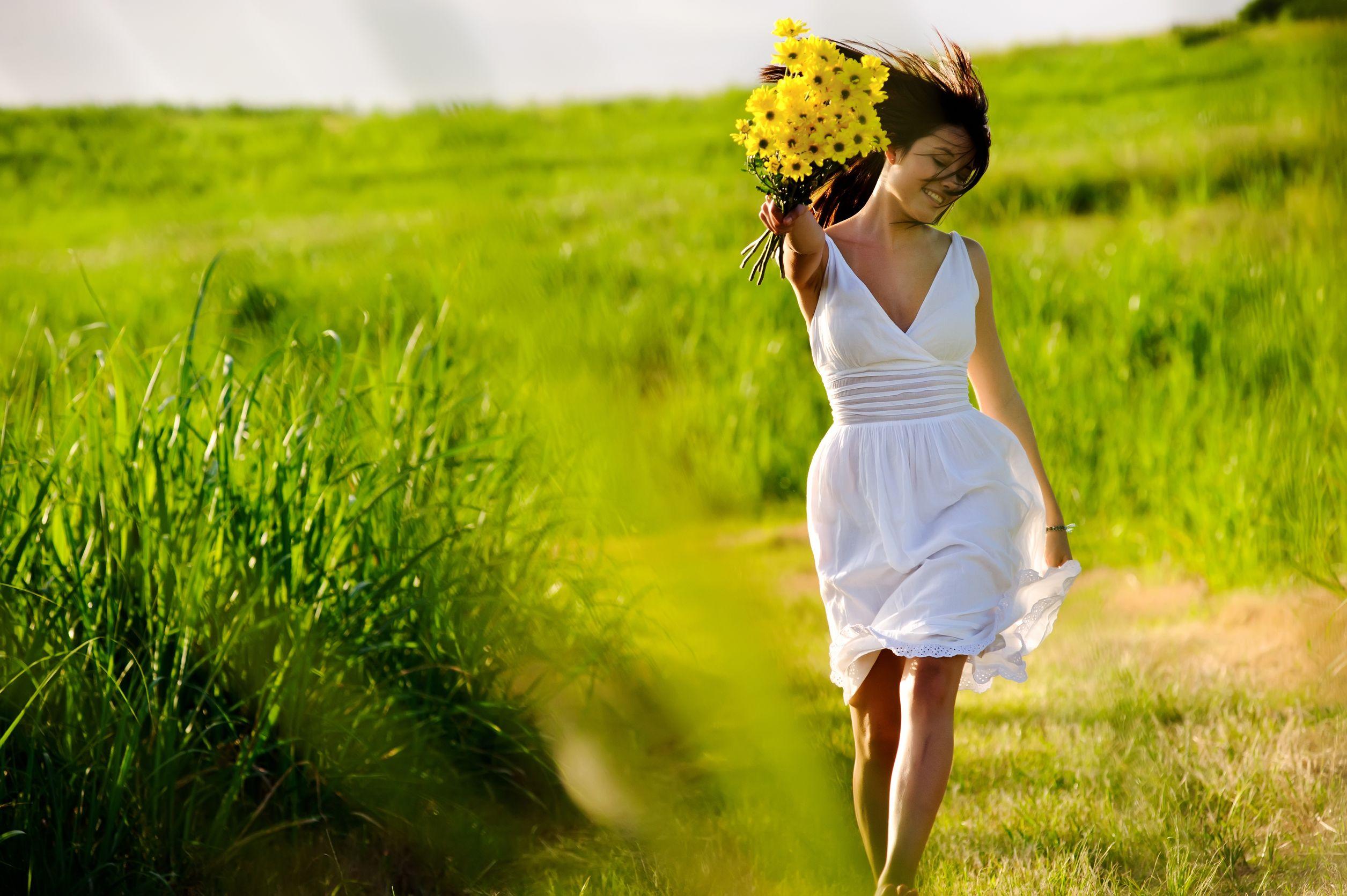 Mulher oriental sorrindo e correndo por um campo enquanto usa um vestido braco e segura um buque de pequenas flores amarelas.
