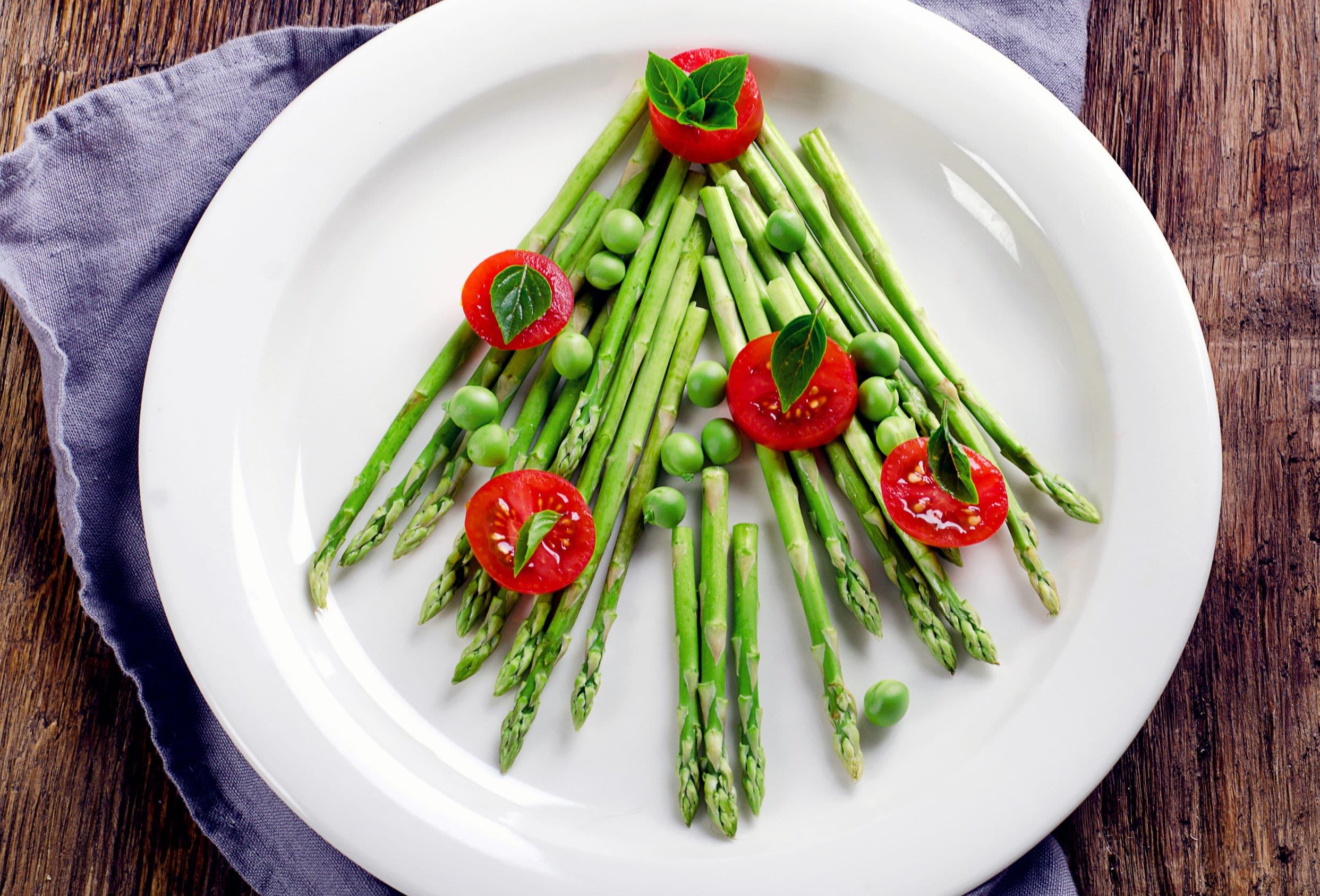 Prato branco em cima de mesa, com aspargos verdes colocados para desenhar uma árvore de natal e tomates cereja colocados como enfeites da árvore.