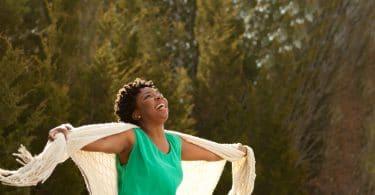 Mulher negra com braços abertos em um cenário de natureza e ar fresco.