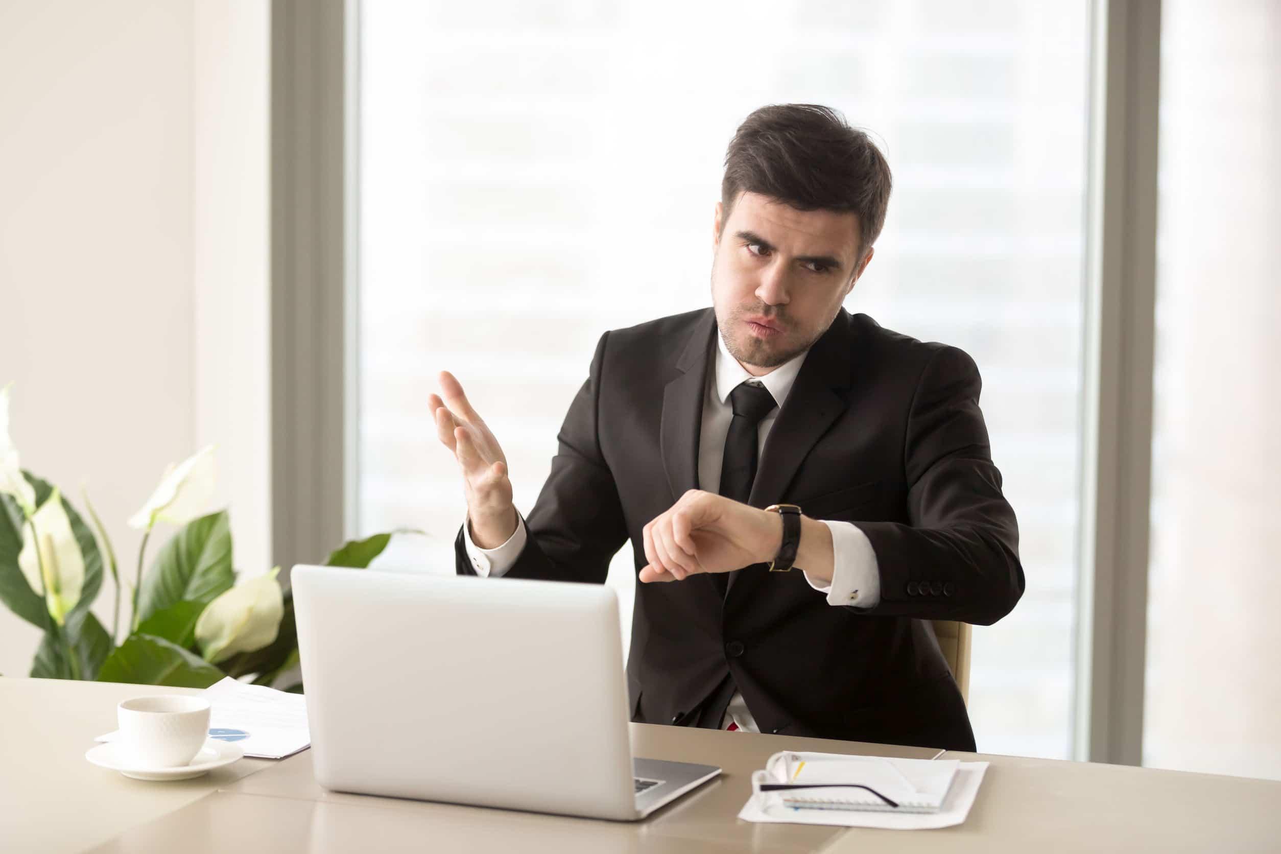 Empresário correndo contra o tempo. Olha para o relógio e faz cara de estressado. Computador na frente dele, muitos papéis na mesa.