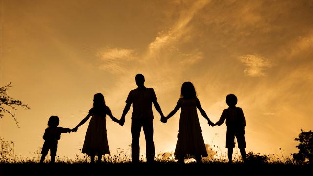 Silhueta de família, com homem, mulher e três crianças, de mãos dadas olhando o pôr do sol.