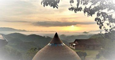 Foto do topo de mosteiro, com pôr do sol ao fundo.
