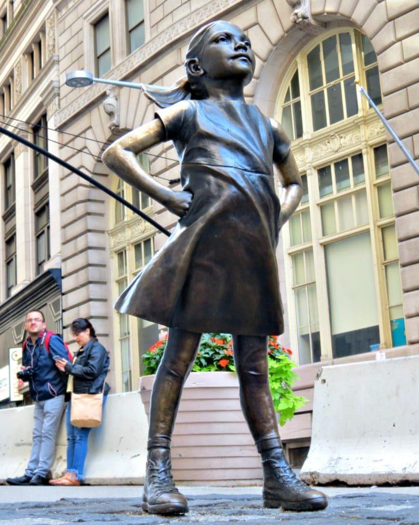 Estátua de uma menina com as mãos na cintura em pose imponente.