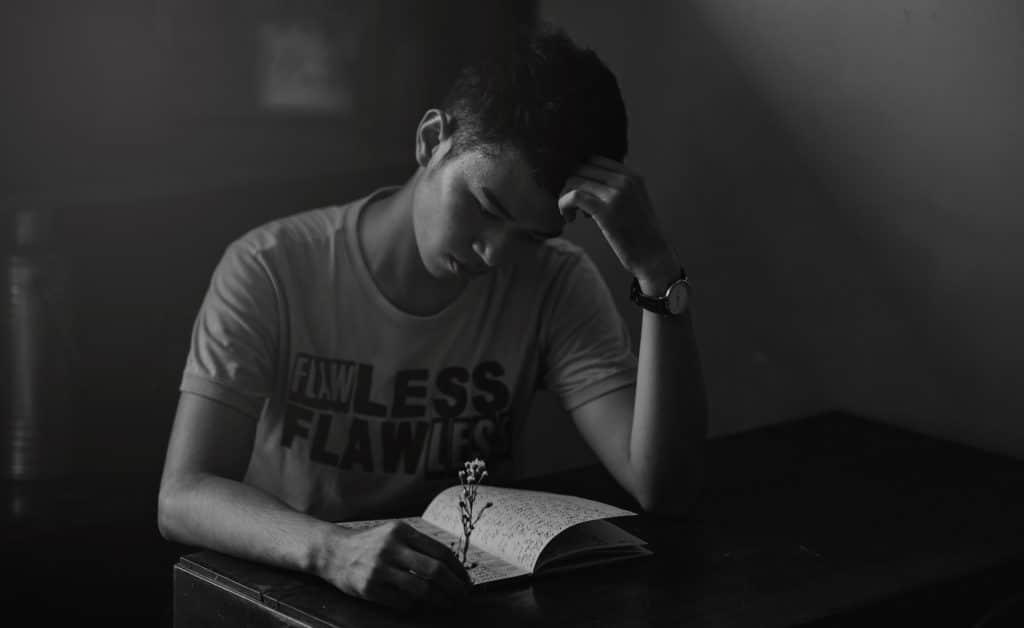 Menino lendo um livro sentado em uma mesa.