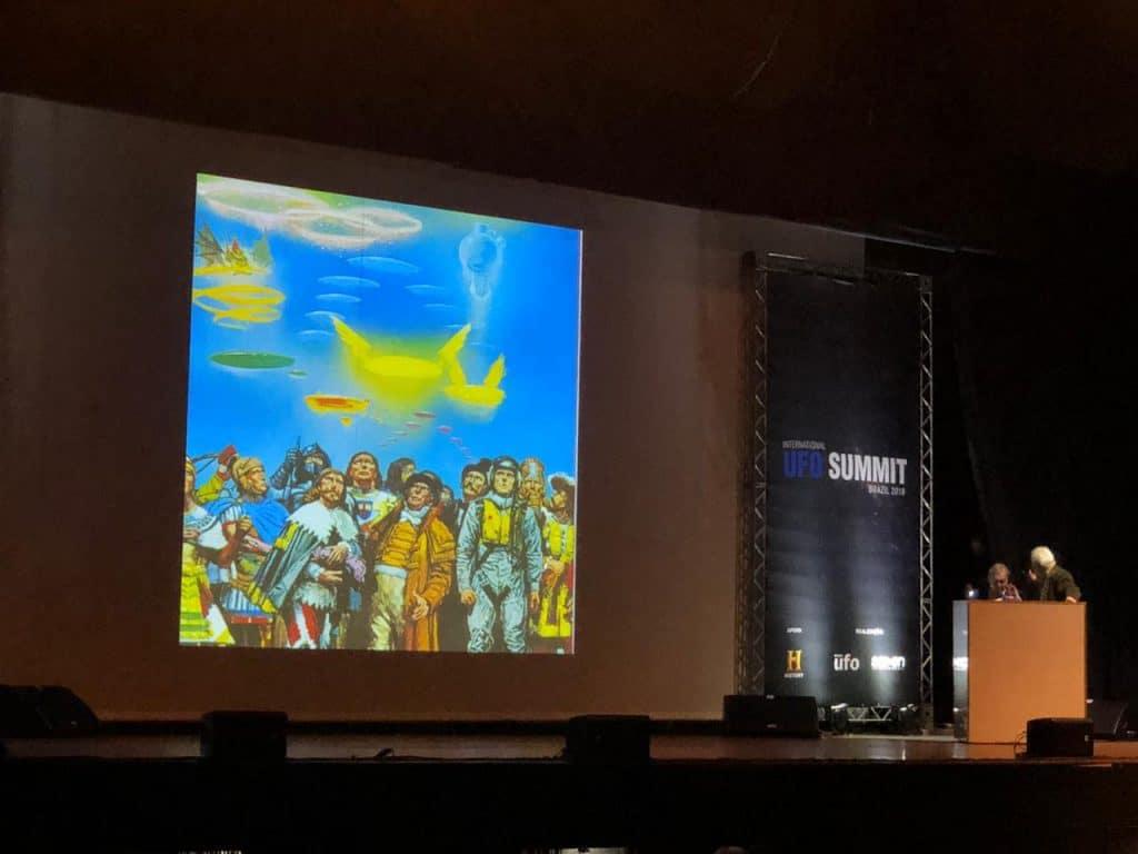 Painel com imagem de pessoas olhando para o céu e alguns discos voadores descendo pelo céu.