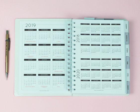Agenda azul de 2019 aberta em folhas de calendários. Uma caneta dourada ao lado.