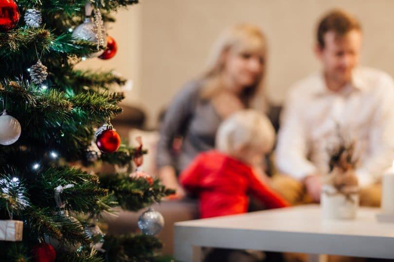 Família reunida em uma mesa e à frente há uma árvore de natal.