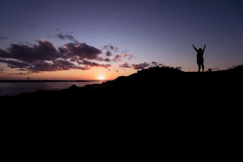 Mulher numa montanha com os braços erguidos em sinal de comemoração.