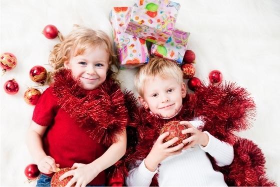 duas crianças pequenas, brancas e loiras, deitadas em um tapete branco, cercadas de enfeites vermelhos de natal e presentes embrulhados.