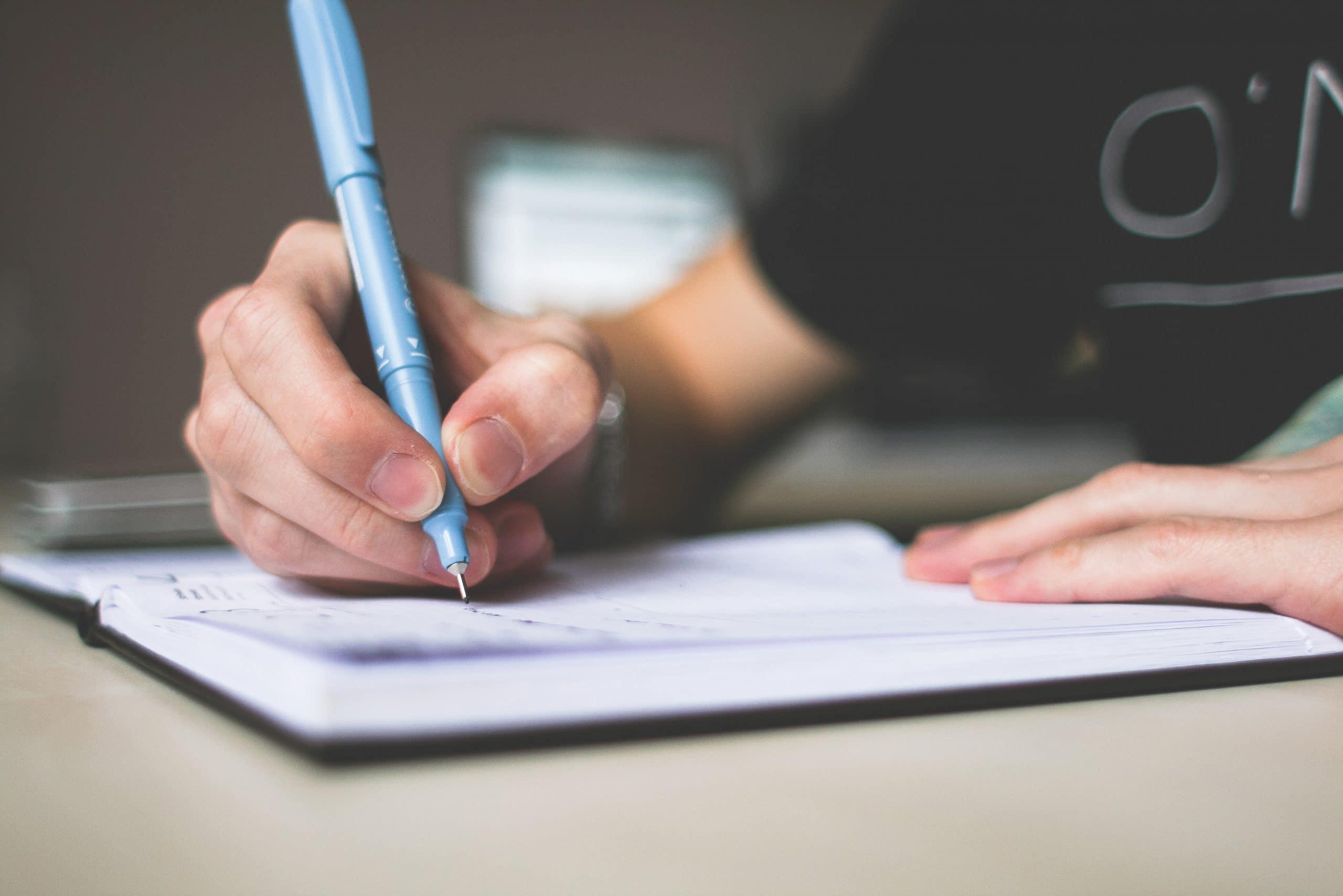 Pessoa escrevendo em caderno. Fazendo lista de desejos para o ano novo. Usa uma caneta azul e uma blusa preta.