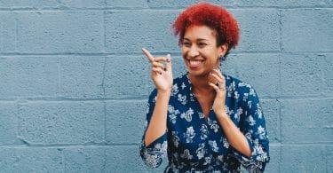 felicidade. Mulher negra de cabelos encaracolados e vermelhos. Ela está sorrindo e apontado para o lado.