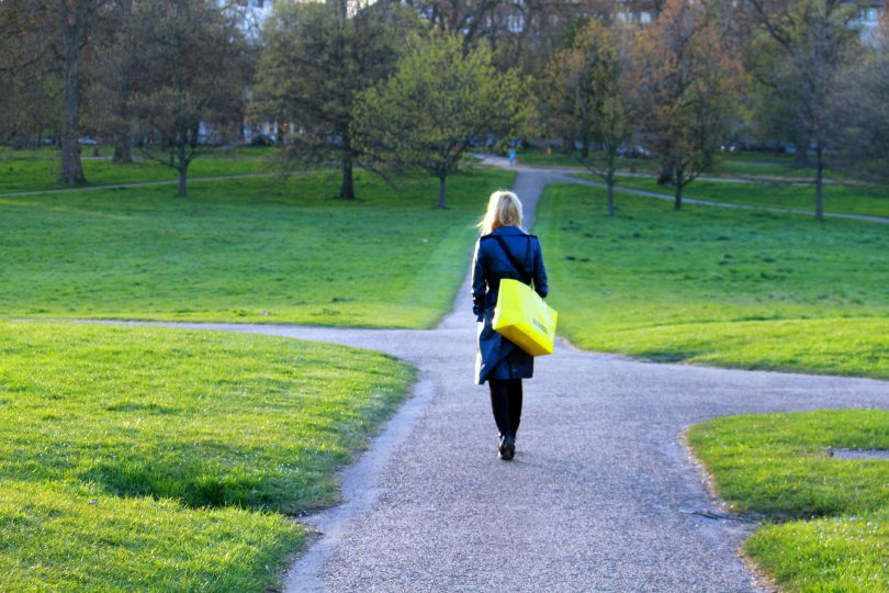 Mulher caminhando em uma estrada que está se dividindo em três novos caminhos.
