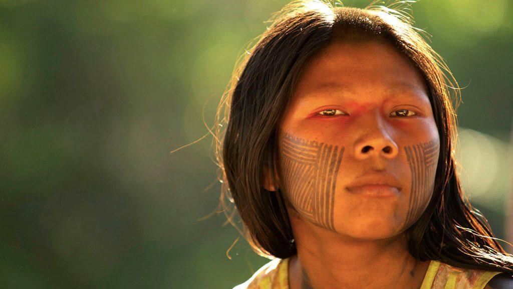 Mulher índia olhando para frente. Ela tem pinturas em seu rosto.