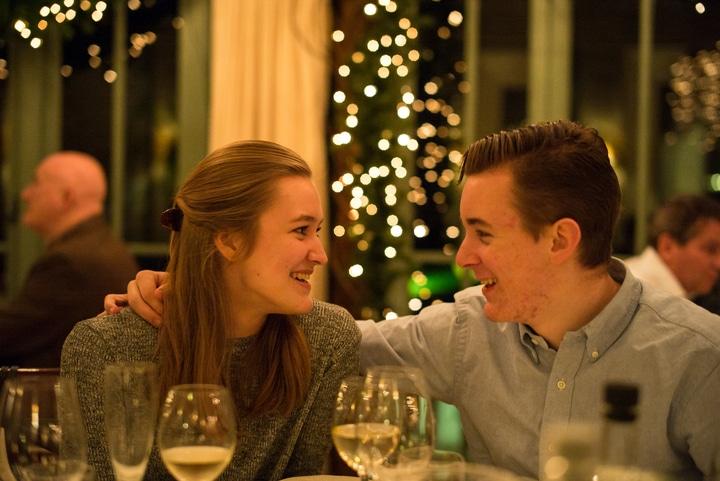 Homem e mulher brancos, jantando na noite de natal, conversando e rindo sentados à mesa.