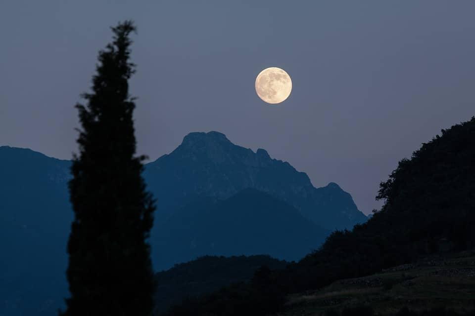 Foto tirada de uma montanha. Lua ao fundo. Paisagem de árvores e montanhas.