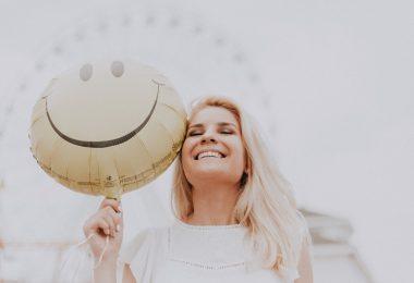 Mulher sorridente em um parque de diversões, posando para foto em frente de uma roda gigante enquanto segura um balão de carinha sorridente.