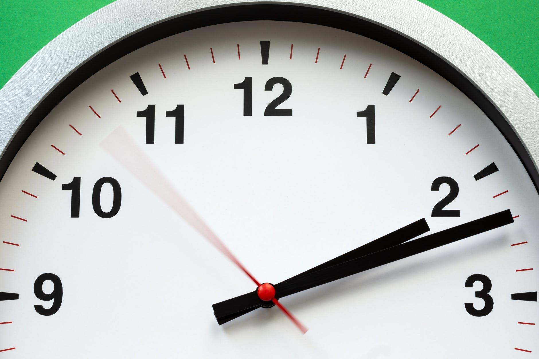 Relógio de parede com os ponteiros indicando 2  e 12 da tarde