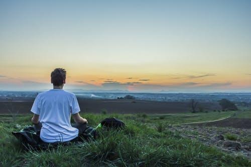 Homem sentado na grama com as pernas cruzadas, meditando e observando o pôr do sol no horizonte.